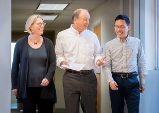 St. Jude researchers Nichols, Robison and Wang walk down a hallway discussing the latest scientific advances.